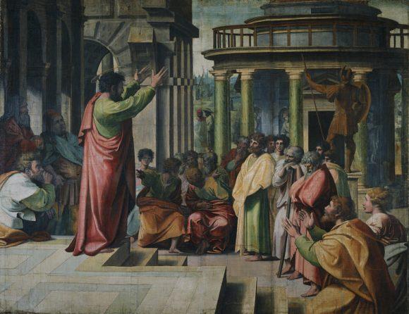 Paulus predikar med upplyfta armar inför åhörare som sitter i en trappa nedanför
