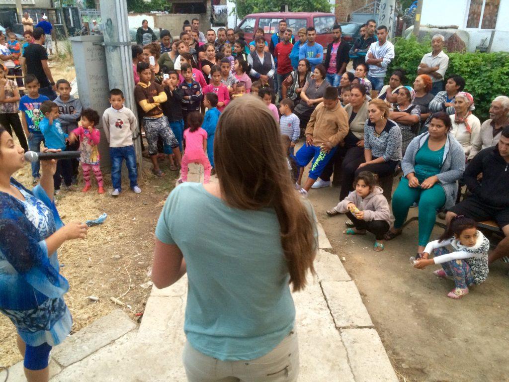 Ung tjej predikar för folkskara i alla åldrar på gatan i en fattig by.