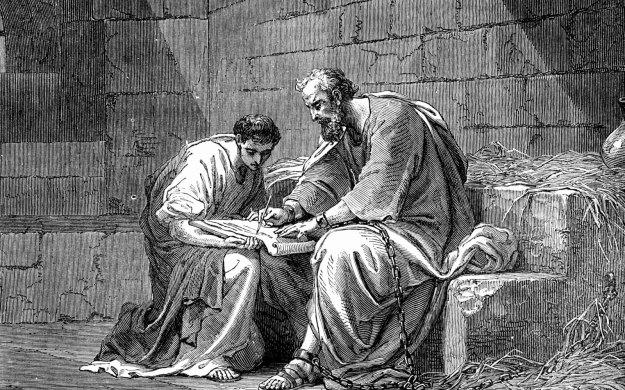 En äldre man skriver och en yngre tittar på
