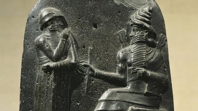 Antik relief. Babylonisk kung sitter på sin tron och har en undersåte framför sig.