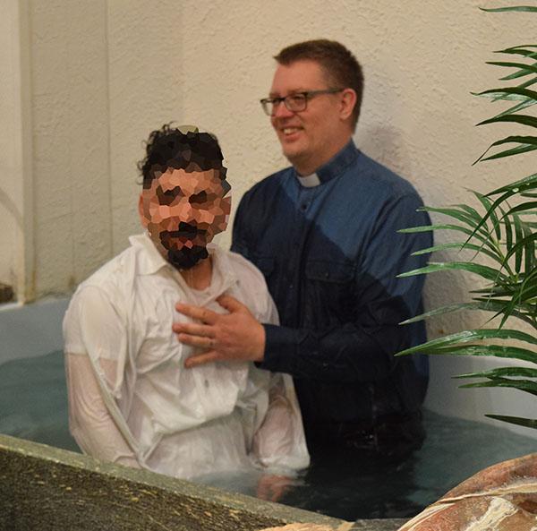 Pastor och nydöpt i dopgrav