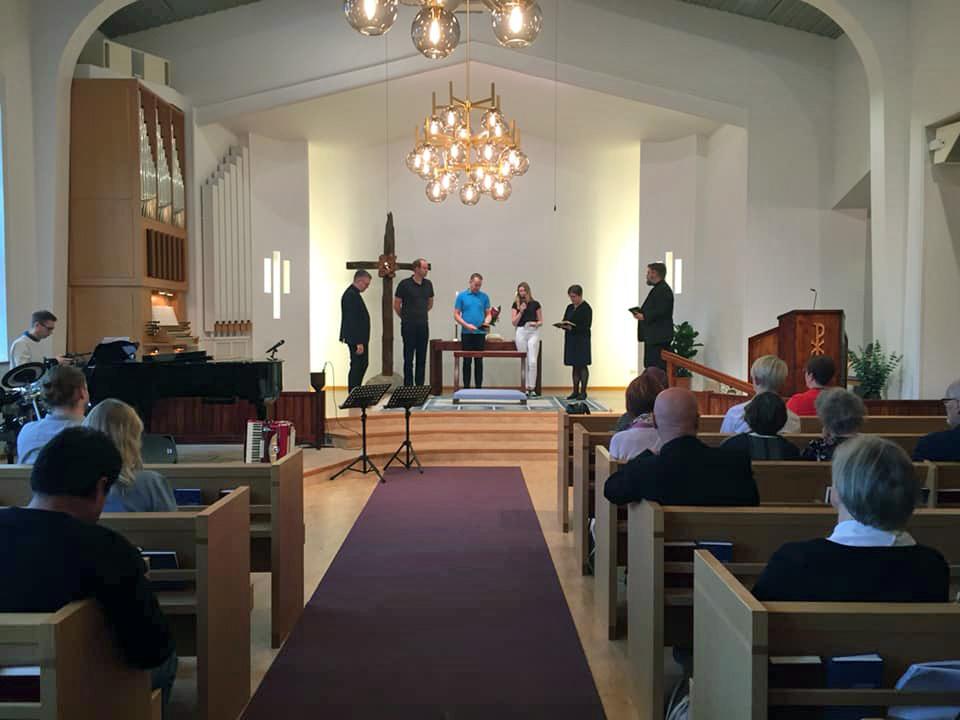 Kyrkolokalen i Hestra, några står längst fram på estraden.